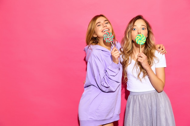 Two young beautiful smiling blond hipster women in trendy summer clothes. carefree hot women posing near pink wall. positive funny models with lollipop
