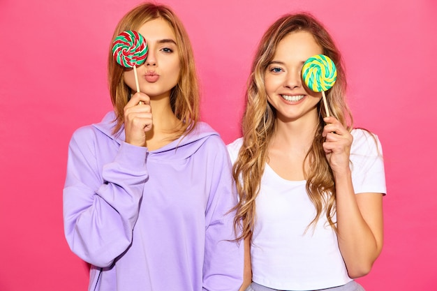 Two young beautiful smiling blond hipster women in trendy summer clothes. carefree hot women posing near pink wall. positive models cover eyes by lollipop