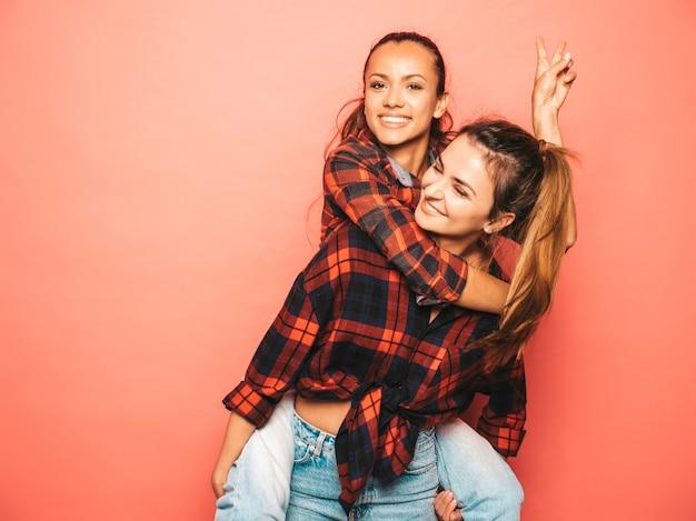 トレンディな同様の格子縞のシャツとジーンズの服の2人の若い美しい笑顔ブルネット流行に敏感な女の子。スタジオでピンクの壁に近いポーズセクシーな屈託のない女性。彼女の友人の背中に座っている正のモデル