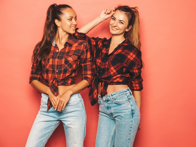 Two young beautiful smiling brunette hipster girls in trendy similar checkered shirt and jeans clothes.sexy carefree women posing near blue wall in studio.positive models having fun