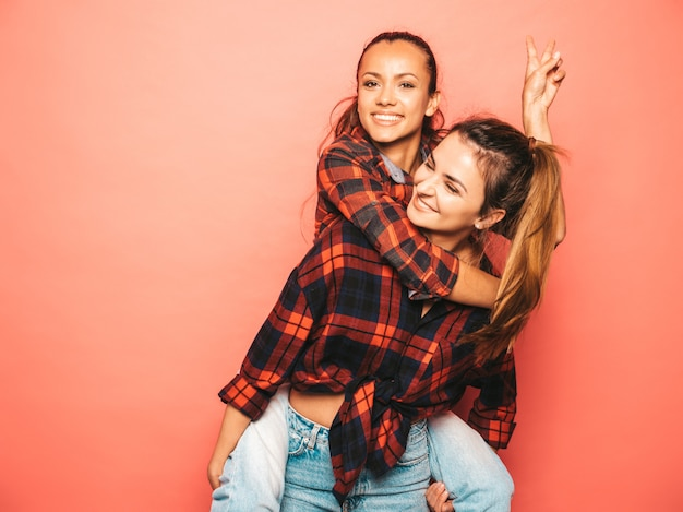 Two young beautiful smiling brunette hipster girls in trendy similar checkered shirt and jeans clothes.sexy carefree women posing near pink wall in studio.positive model sitting on her friend back