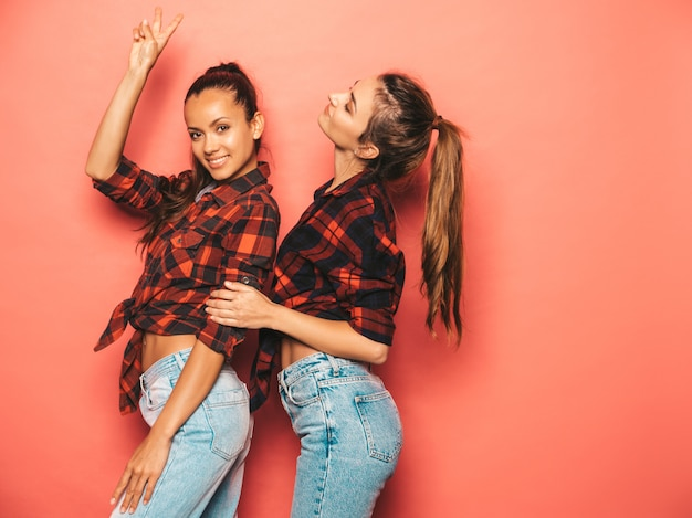 Two young beautiful smiling brunette hipster girls in trendy similar checkered shirt and jeans clothes.sexy carefree women posing near pink wall in studio.positive models having fun
