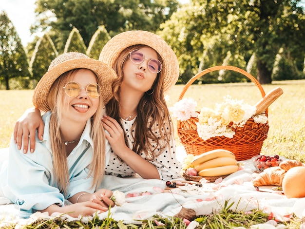 Две молодые красивые улыбающиеся женщины в модном летнем сарафане и шляпах. беззаботные женщины делают пикник на улице.