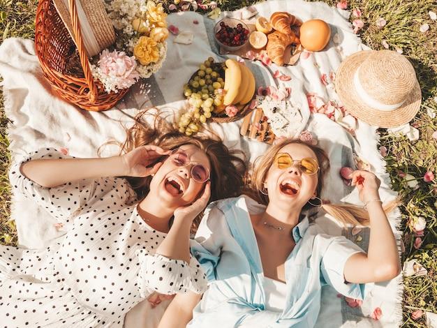 트렌디한 여름 sundress와 모자에 두 젊은 아름 다운 웃는 여성. 바깥에서 피크닉을 만드는 평온한 여성.