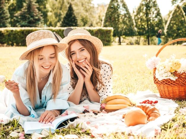 Due giovani belle donne sorridenti in prendisole e cappelli estivi alla moda. donne spensierate che fanno picnic all'esterno.