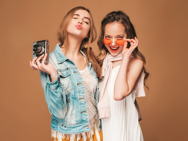 Две молодые красивые улыбающиеся девушки в модной летней повседневной одежды и солнцезащитные очки. сексуальные беззаботные женщины позируют. фотографировать на ретро камеру