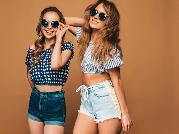 トレンディな夏服とサングラスで2人の若い美しい笑顔の女の子。セクシーな屈託のない女性がポーズします。ポジティブモデル