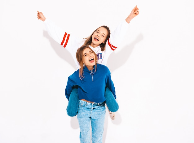Две молодые красивые улыбающиеся девушки в модной летней одежде. беззаботные женщины. позитивная модель сидит на спине подруги и поднимает руки