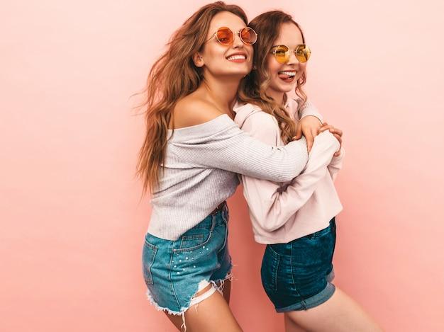 トレンディな夏服の2人の若い美しい笑顔の女の子。セクシーな屈託のない女性がポーズします。楽しいポジティブモデル