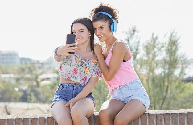 Две молодые красивые улыбающиеся девушки, делающие селфи фото