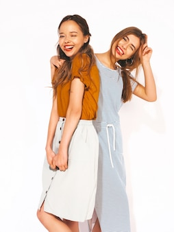 Two young beautiful smiling girls in trendy summer casual clothes. sexy carefree women. positive models. winking