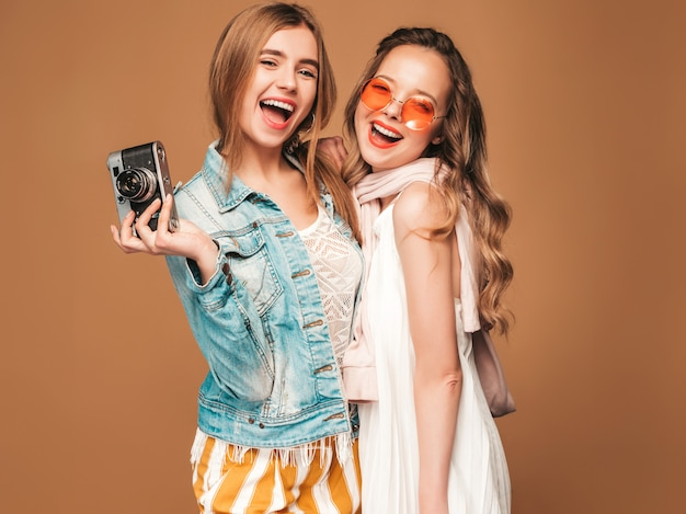 Two young beautiful smiling girls in trendy summer casual clothes and sunglasses. sexy carefree women posing. taking pictures on retro camera
