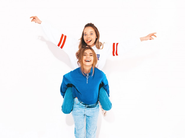 Two young beautiful smiling girls in trendy summer clothes. carefree women. positive model sitting on her friend's back and raising hands