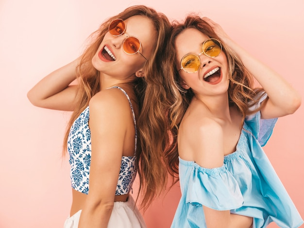 Two young beautiful smiling girls in trendy summer clothes. sexy carefree women posing. positive models having fun