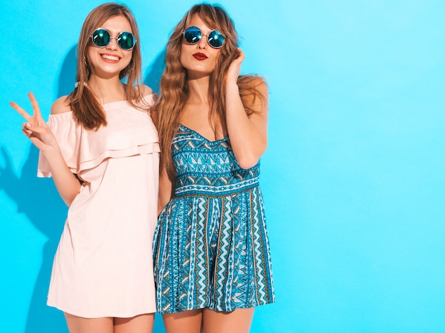 Two young beautiful smiling girls in trendy summer dresses and sunglasses. sexy carefree women posing. positive models