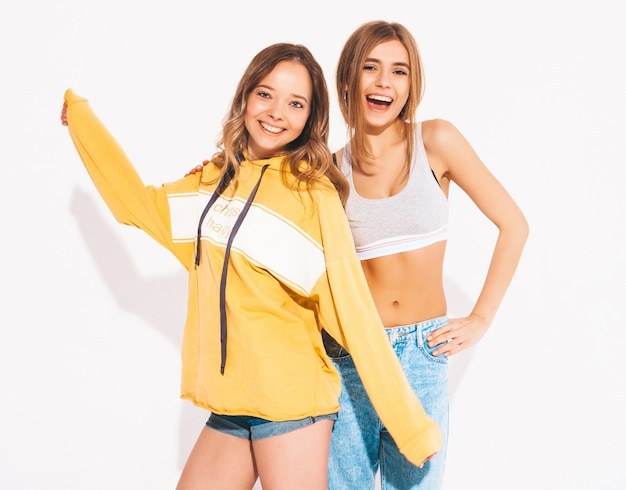 Two young beautiful smiling girls in trendy summer jeans clothes. sexy carefree women. positive models