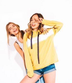 Two young beautiful smiling girls in trendy summer jeans clothes and yellow hoodie. carefree women. positive models