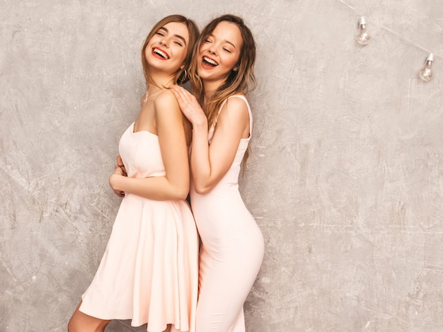 Two young beautiful smiling girls in trendy summer light pink dresses. sexy carefree women posing. positive models having fun
