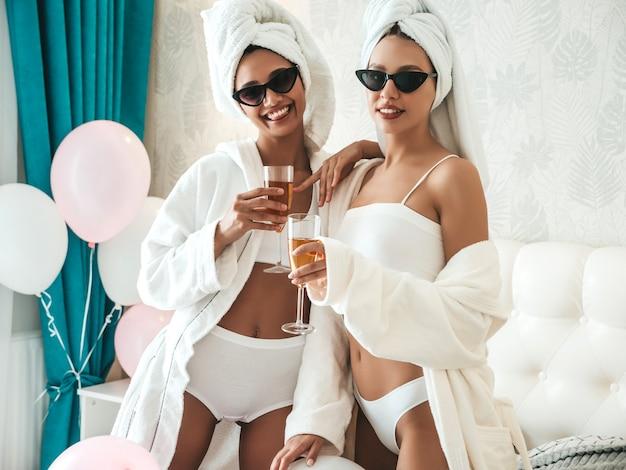 Due giovani belle ragazze sorridenti in accappatoi bianchi e asciugamani sulla testa