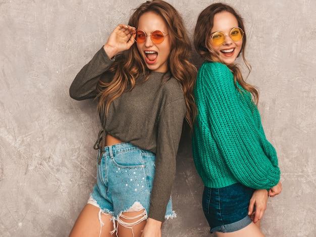 トレンディな夏服で2人の若い美しい笑顔の豪華な女の子。セクシーな屈託のない女性がポーズします。ラウンドサングラスを楽しんでいる肯定的なモデル