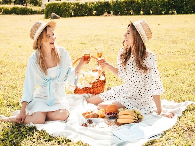 Две молодые красивые улыбающиеся хипстерские женщины в летнем сарафане и шляпах. беззаботные женщины делают пикник на улице.
