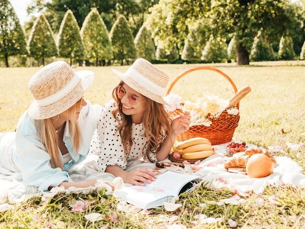 夏のサンドレスと帽子の2人の若い美しい笑顔の流行に敏感な女性。外でピクニックをするのんきな女性。