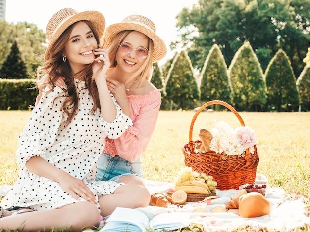 여름 sundress와 모자에 두 젊은 아름 다운 웃는 hipster 여성. 바깥에서 피크닉을 만드는 평온한 여성.