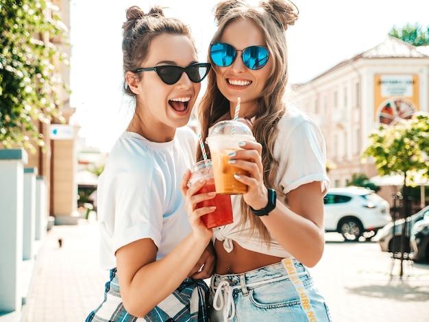 トレンディな夏の服を着た2人の若い美しい笑顔の流行に敏感な女性
