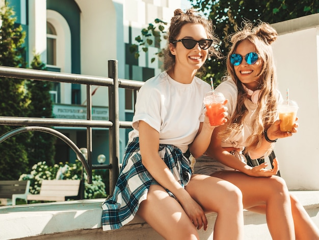 Две молодые красивые улыбающиеся хипстерские девушки в модной летней одежде