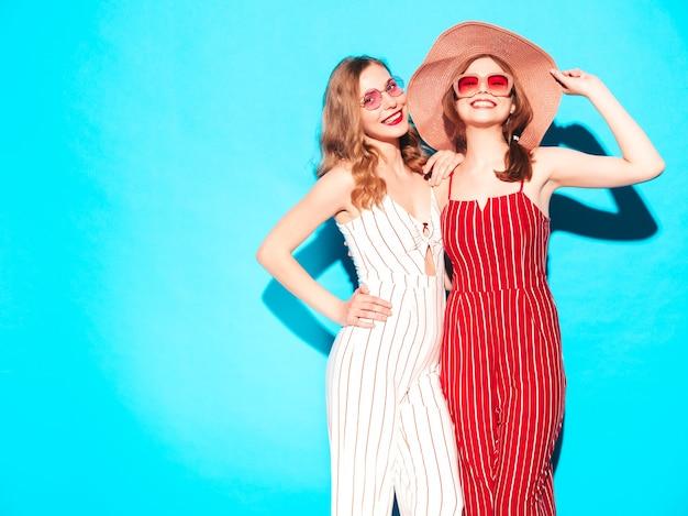 Две молодые красивые улыбающиеся хипстерские девушки в модных летних комбинезонах