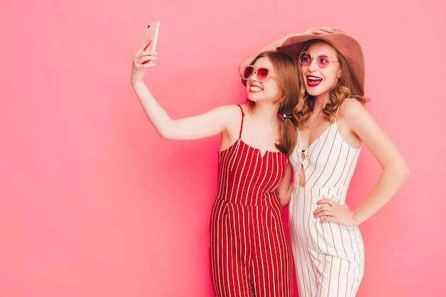 トレンディな夏のオーバーオールの服を着た2人の若い美しい笑顔の流行に敏感な女性