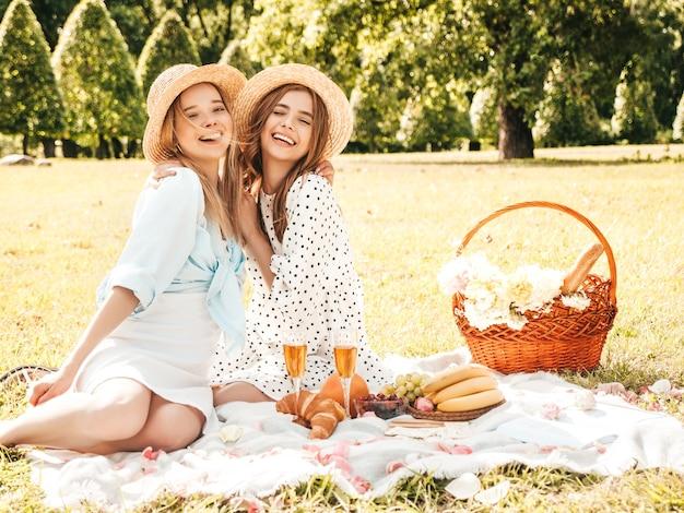 Две молодые красивые улыбающиеся хипстерские девушки в модном летнем сарафане и шляпах. беззаботные женщины, делающие пикник.