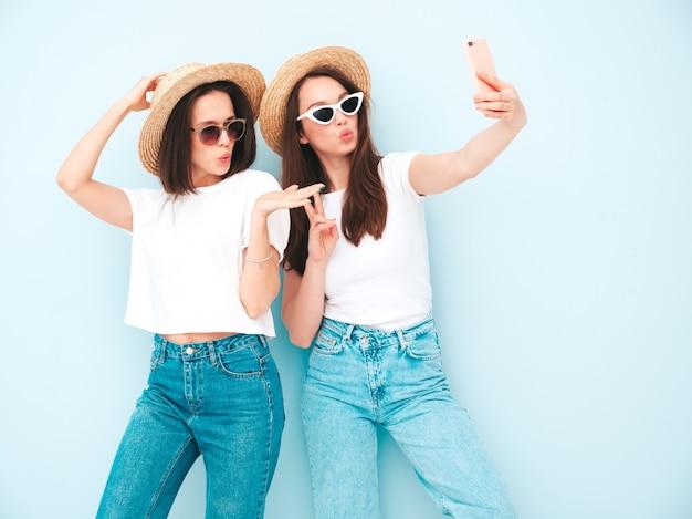トレンディな夏の白いtシャツとジーンズの服を着た2人の若い美しい笑顔の流行に敏感な女性