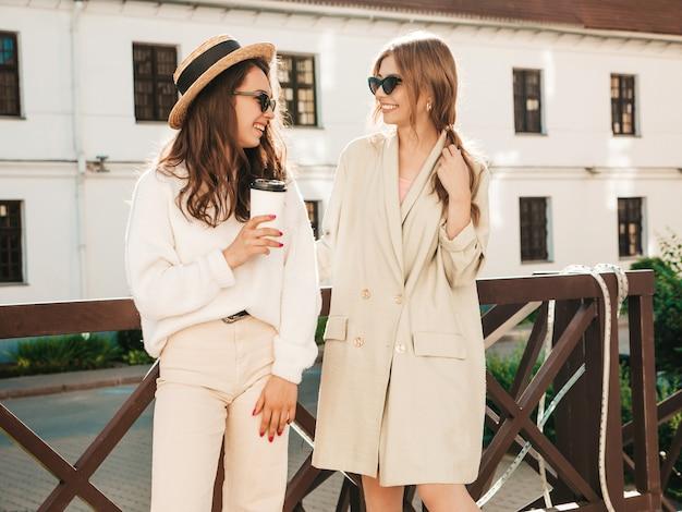 トレンディな白いセーターとコートで2人の若い美しい笑顔の流行に敏感な女性