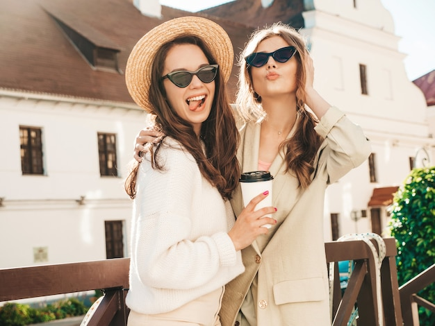트렌디한 흰색 스웨터와 코트를 입은 두 젊은 아름다운 웃는 힙스터 여성