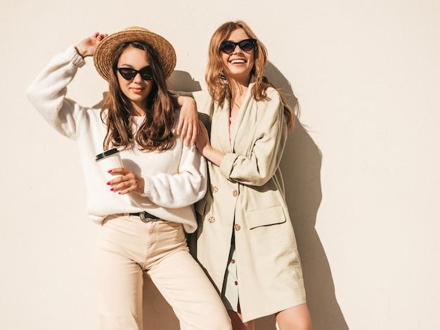 Две молодые красивые улыбающиеся хипстерские девушки в модном белом свитере и пальто
