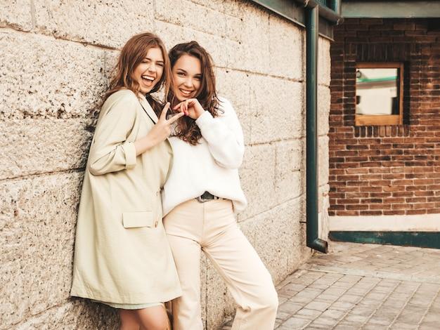 Две молодые красивые улыбающиеся хипстерские девушки в модном белом свитере и пальто Бесплатные Фотографии