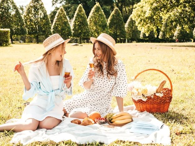 Due giovani belle donne sorridenti hipster in prendisole e cappelli estivi. donne spensierate che fanno picnic all'esterno.