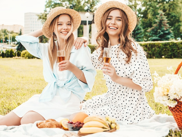 Two young beautiful smiling hipster female in summer sundress and hats.carefree women making picnic outside.