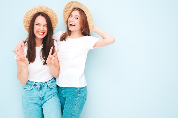 Two young beautiful smiling hipster female in trendy same summer white t-shirt and jeans clothes