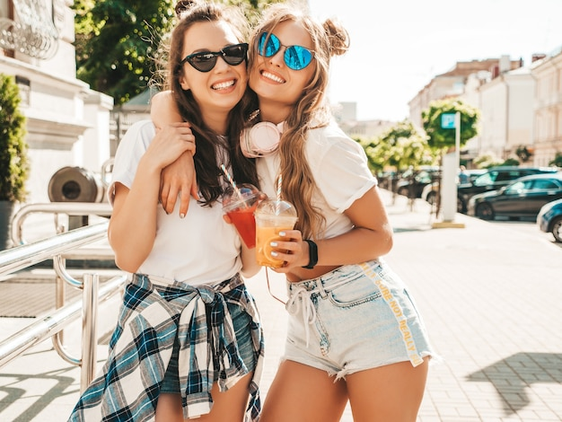 Two young beautiful smiling hipster female in trendy summer clothes