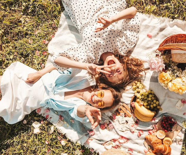 Two young beautiful smiling hipster female in trendy summer sundress and hats.carefree women making picnic outside.