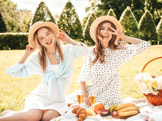 Two young beautiful smiling hipster female in trendy summer sundress and hats.carefree women making picnic.