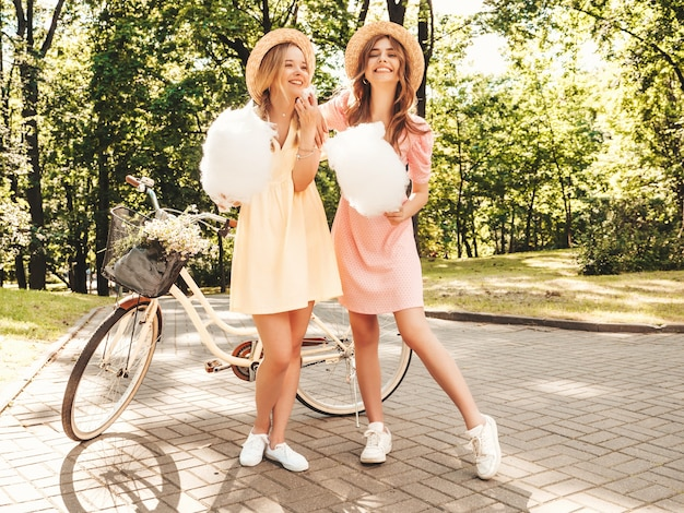 Two young beautiful smiling hipster female in trendy summer sundress