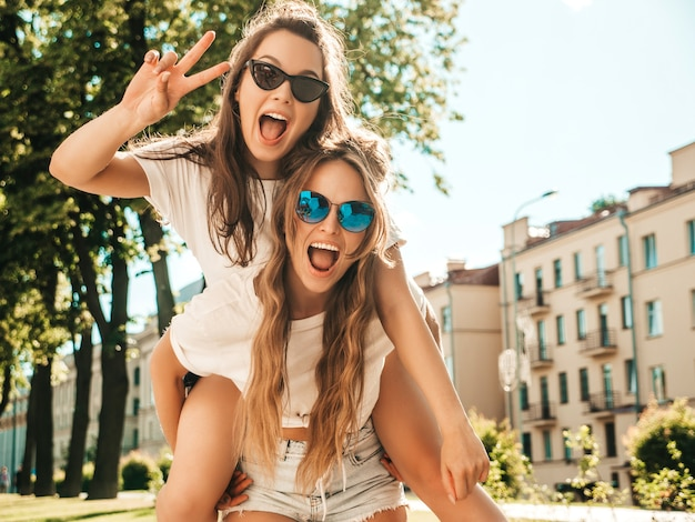 Two young beautiful smiling hipster female in trendy summer white t-shirt clothes