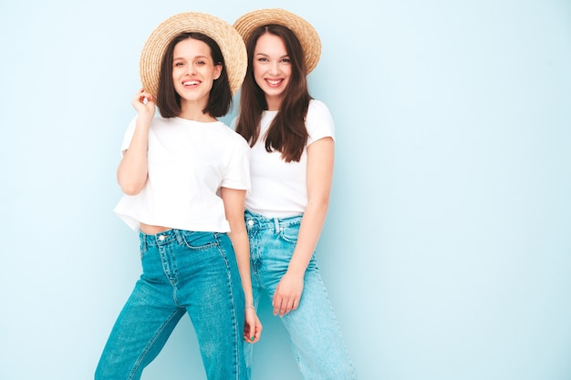 Two young beautiful smiling hipster female in trendy summer white t-shirt and jeans clothes