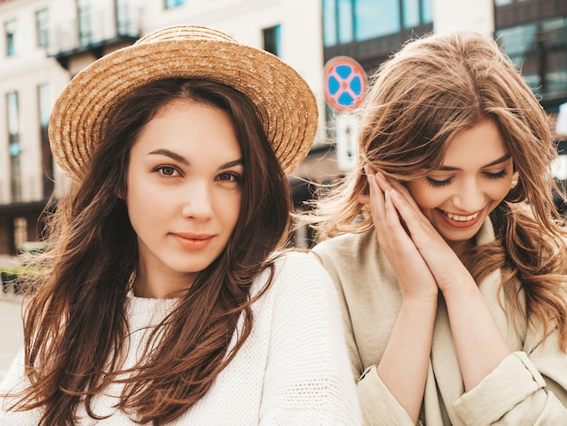 Two young beautiful smiling hipster female in trendy white sweater and coat