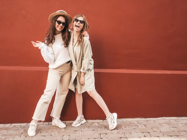 Due giovani belle donne hipster sorridenti in maglione e cappotto bianchi alla moda