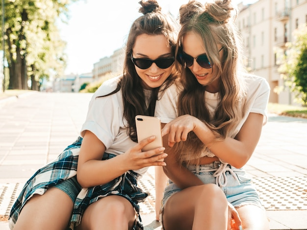 Two young beautiful smiling hipster female
