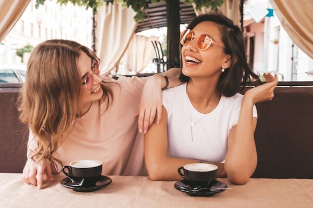 トレンディな夏のカジュアルな服装で2人の若い美しい笑顔の流行に敏感な女の子。ベランダテラスカフェでおしゃべりとコーヒーを飲んで屈託のない女性。
